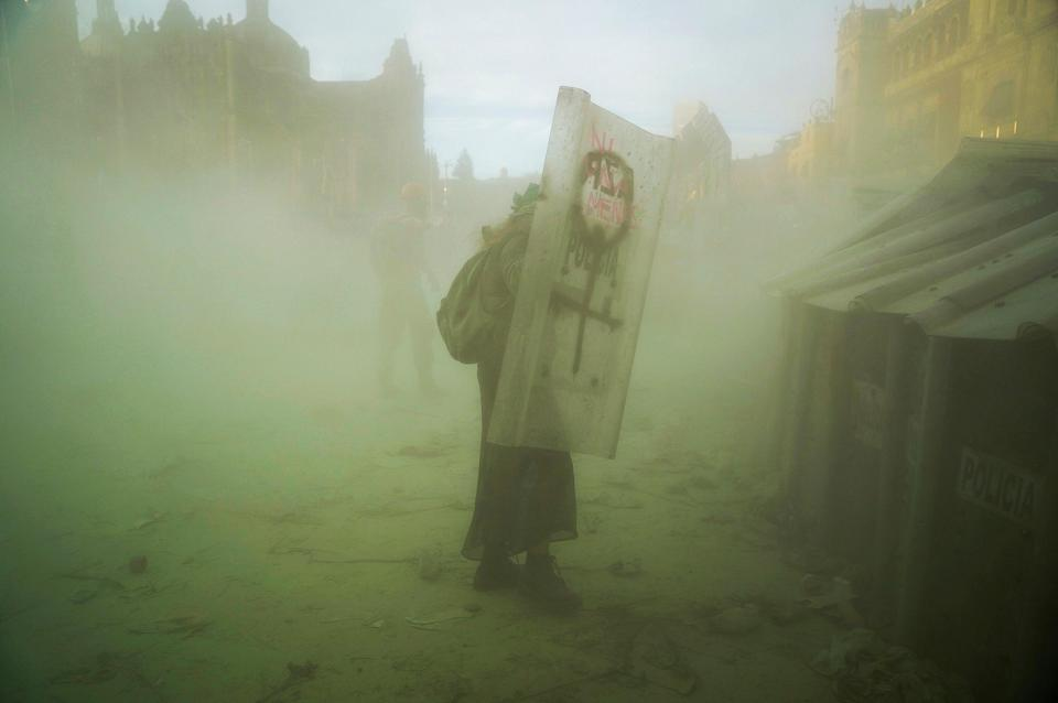 A woman takes cover behind a shieldREUTERS
