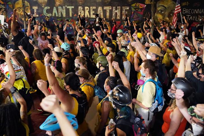 Protesters march past a mural of George Floyd's last words on their way to the Mark O. Hatfield U.S. Courthouse on July 20, 2020, in Portland, Ore. George Floyd died in Minneapolis in police custody.