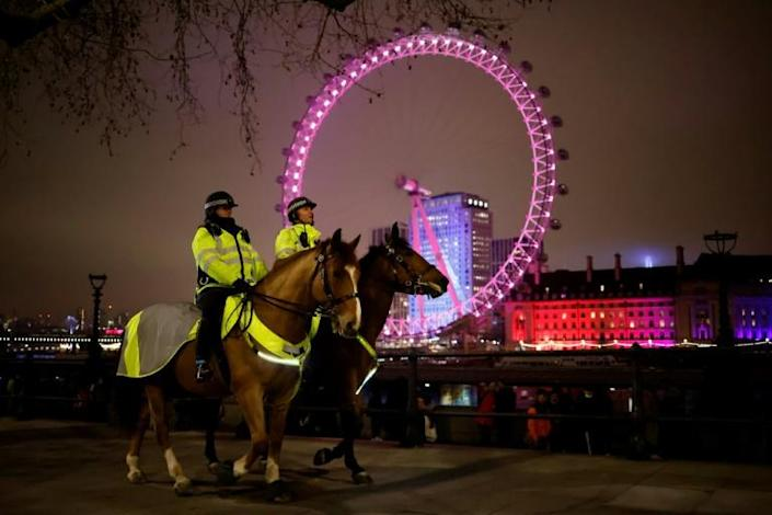 Mounted police officers patrol The Victoria Embankment opposite the London Eye in a near-deserted London late on New Year's Eve, December 31, 2020, as authorities in the Tier 4 city hope the message to stay at home is obeyed