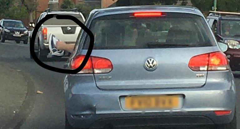 A car with an iron sticking out the window.