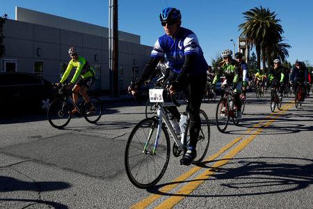 A cyclist rides his bike with a placard in honor of shooting victim Yvette Velasco during the San Bernardino Police Department IRC Memorial Bike Ride on the one year anniversary of the San Bernardino attack in San Bernardino, California, U.S. December 2, 2016.  REUTERS/Patrick T. Fallon