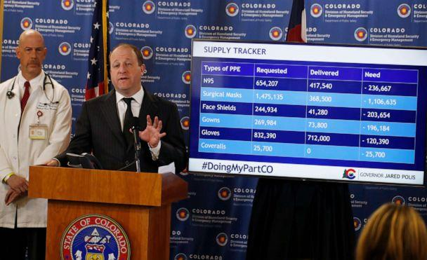 PHOTO: Colorado Gov. Jared Polis, front, makes a point as Dr. Marc Moss, a professor at the University of Colorado, looks on during a news conference on the spread of the new coronavirus Monday, March 30, 2020, in Centennial, Colo. (David Zalubowski/AP)