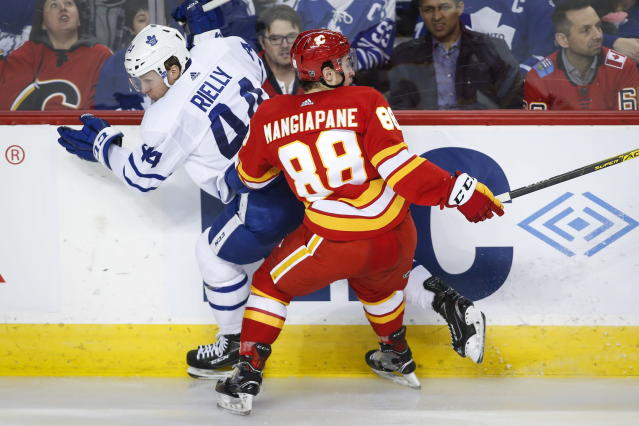 Toronto Maple Leafs' Morgan Rielly, left, is checked by Calgary Flames' Andrew Mangiapane during the third period of an NHL hockey game, Thursday, Dec. 12, 2019 in Calgary, Alberta. (Jeff McIntosh/The Canadian Press via AP)
