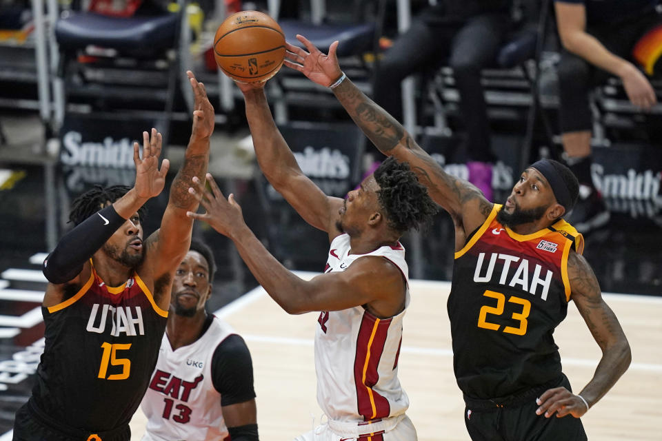 Utah Jazz's Derrick Favors (15) and Royce O'Neale (23) defend against Miami Heat forward Jimmy Butler, center, in the second half during an NBA basketball game Saturday, Feb. 13, 2021, in Salt Lake City. (AP Photo/Rick Bowmer)