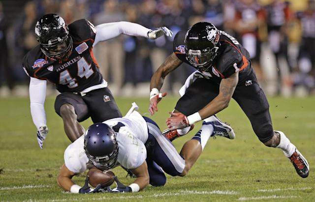 Utah State receiver Shaan Johnson beats Northern Illinois defensive end Perez Ford, left, and safety Dechane Durante to a fumbled ball during the first half of the Poinsettia Bowl NCAA college football game Thursday, Dec. 26, 2013, in San Diego. (AP Photo/Lenny Ignelzi)