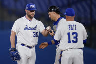 Israel's Jeremy Bleich, left hands the ball to manager Eric Holtz, right, as Ryan Lavarnway looks on during the sixth inning of a baseball game against the United States at the 2020 Summer Olympics, Friday, July 30, 2021, in Yokohama, Japan. (AP Photo/Sue Ogrocki)