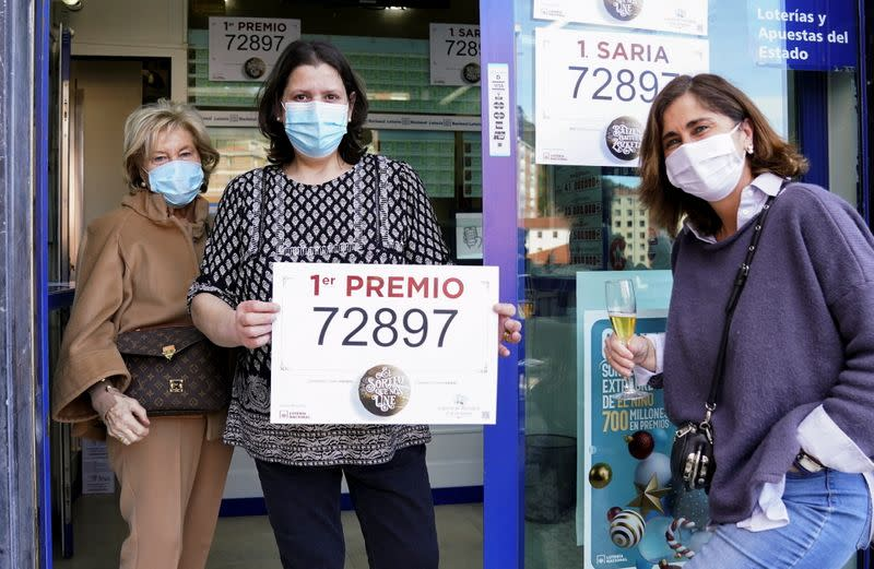 """Lottery shop owner Monica Cejudo holds up a First Prize winning ticket of Spain's Christmas Lottery """"El Gordo"""" (The Fat One), alongside family members, in Bilbao"""