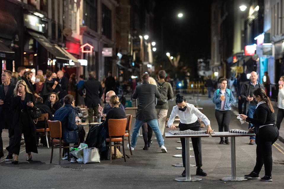 Staff pack seating outside bars in Soho, London the day after pubs and restaurants were subject to a 10pm curfew to combat the rise in coronavirus cases in England. (Photo by Dominic Lipinski/PA Images via Getty Images)