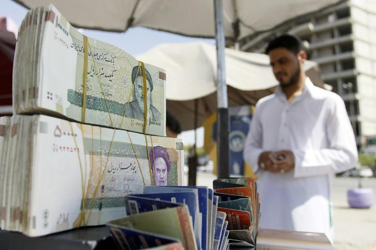 A vendor in Iraq's shrine city of Najaf sells Iranian rials, which have lost half their value against the dollar since April, slashing Iranian pilgrims' buying power