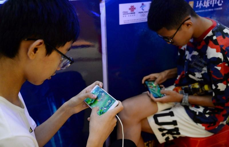 "FILE PHOTO: Young people play the game ""Honour of Kings"" by Tencent, during an event inside a shopping mall in Handan, Hebei"