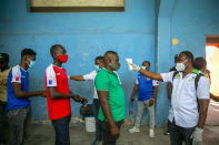 Health ministry workers check the temperature of mask-wearing fans as a precaution against the spread of the new coronavirus, before entering the stadium prior to the start of the CONCACAF World Cup qualifying soccer match between Haiti and Belize in Port-au-prince, Haiti, Thursday, March 25, 2021. ( AP Photo/Dieu Nalio Chery)