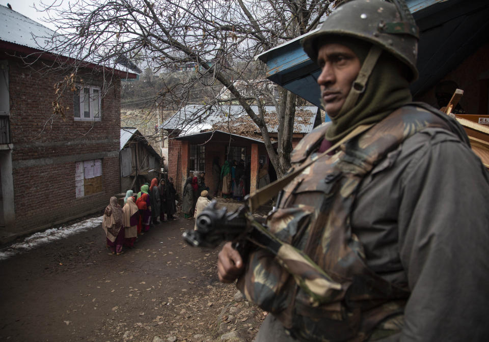A soldier stands guard as Kashmiris stand in a queue to cast their votes during the first phase of District Development Councils election on the outskirts of Srinagar, Indian controlled Kashmir, Saturday, Nov. 28, 2020. Thousands of people in Indian-controlled Kashmir voted Saturday amid tight security and freezing cold temperatures in the first phase of local elections, the first since New Delhi revoked the disputed region's semiautonomous status. (AP Photo/Mukhtar Khan)