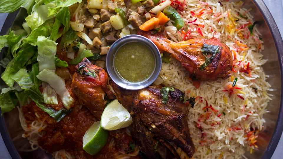 A platter for two with rice, pasta, hilib (lamb), chicken and beef suqaar at a Somali restaurant in Maine, the US