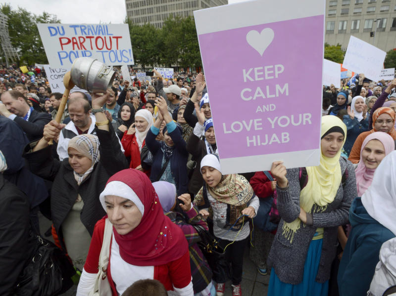 """Demonstrators take part in a protest against Quebec's proposed """"charter of values"""" in Montreal on Saturday Sept. 14, 2013. The plan by the ruling party, the separatist Parti Quebecois, to make the provincial government religion-neutral, is trying to ban some symbols of religious faith such as Jewish skullcaps, Sikh turbans, Muslim head scarves and large crucifixes from public work places. (AP Photo/The Canadian Press, Ryan Remiorz)"""