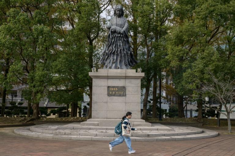 A woman runs past a monument to the atomic bombing in Nagasaki