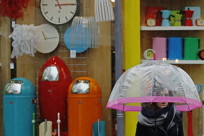 A woman carrying an umbrella passes a shop selling household goods, in Brighton