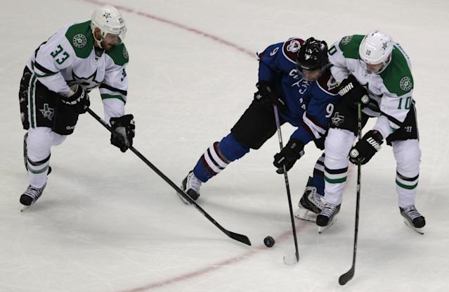 Dallas Stars defenseman Alex Goligoski (33) reaches for the puck against Colorado Avalanche center Matt Duchene (9) as Stars center Shawn Horcoff (10) defends Duchene in the first period of a hockey game in Denver on Tuesday, Oct. 15, 2013. Colorado won 3-2. (AP Photo/Joe Mahoney)