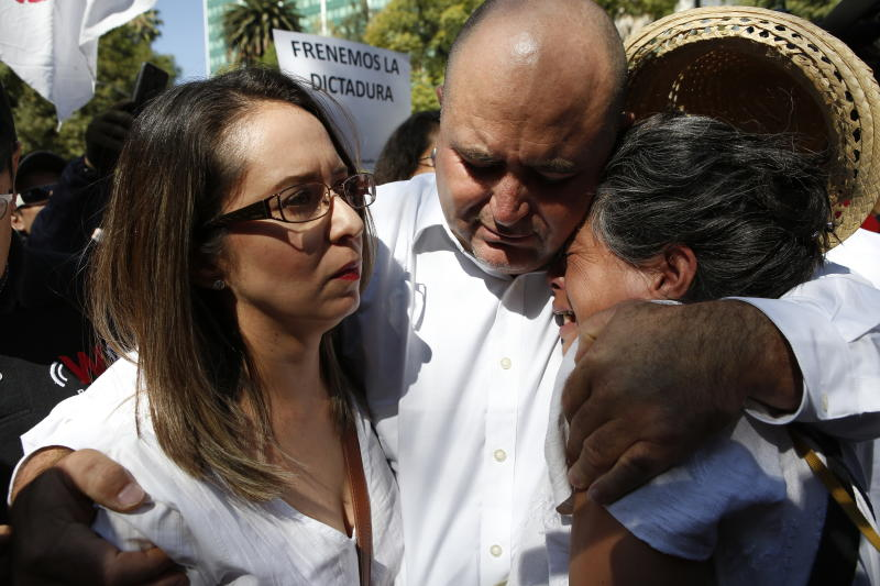 Julian LeBaron, center, embraces Erika Garcia, left, and another woman before a protest against the first year in office of Mexico's President Andres Manuel Lopez Obrador, in Mexico City, Sunday, Dec. 1, 2019. LeBaron joined a protest on Reforma avenue, to expressed anger and frustration over increasingly appalling incidents of violence, a stagnant economy and deepening political divisions in the country. (AP Photo/Ginnette Riquelme)