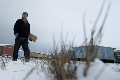 In this Oct. 8, 2014 photo, Democratic party canvasser Gabe Tegoseak travels door to door through Barrow, Alaska, to promote U.S. Sen. Mark Begich's candidacy. He works for the Alaska Democratic Party. His shoe-leather campaign outreach is political ground game on a local level that's shorthand for getting your voters to actually cast a ballot for your candidate. (AP Photo/Gregory Bull)