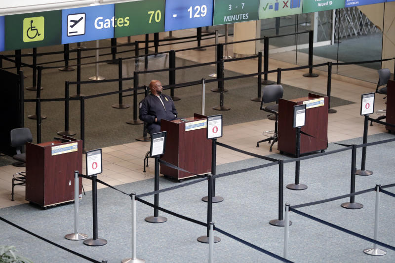 Lines that would normally be full of people waiting to go their boarding gates are now empty as a lone TSA agent on duty for security reasons sits at Orlando International Airport that is closed due to the anticipated arrival of Hurricane Dorian on the East Coast Tuesday, Sept. 3, 2019, in Orlando, Fla. (AP Photo/John Raoux)