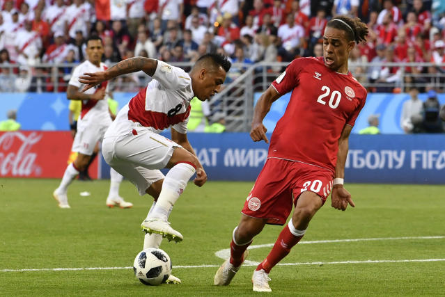 Peru's Christian Cueva, left, duels for the ball with Denmark's Yussuf Yurary Poulsen during the group C match between Peru and Denmark at the 2018 soccer World Cup in the Mordovia Arena in Saransk, Russia, Saturday, June 16, 2018. (AP Photo/Martin Meissner)