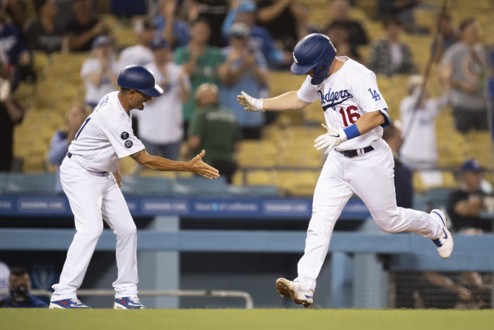 Los Angeles Dodgers' Will Smith, right, celebrates his two-run home run with third base coach Dino Ebel during the fourth inning of a baseball game against the Philadelphia Phillies in Los Angeles, Monday, June 14, 2021. (AP Photo/Kyusung Gong)