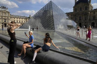 Visitors take a break outside the Louvre Museum courtyard, in Paris, Wednesday, June 9, 2021. France is back in business as a tourist destination after opening its borders Wednesday to foreign visitors who are inoculated against the coronavirus with vaccines approved by the European Union's medicines agency. France's acceptance of only the Pfizer, Moderna, AstraZeneca and Johnson & Johnson vaccines means that tourism is still barred for would-be visitors from China and other countries that use other vaccines. (AP Photo/Francois Mori)