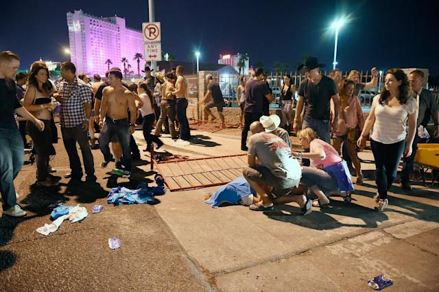 <p>People tend to the wounded outside the Route 91 Harvest Country music festival grounds after an apparent shooting on Oct. 1, 2017 in Las Vegas, Nevada. (Photo: David Becker/Getty Images) </p>