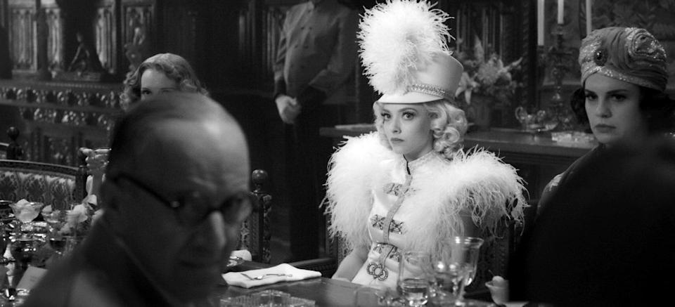 MANK, Arliss Howard (glasses) as Louis B. Mayer, Amanda Seyfried (in white) as Marion Davies, 2020.  Netflix / Courtesy Everett Collection