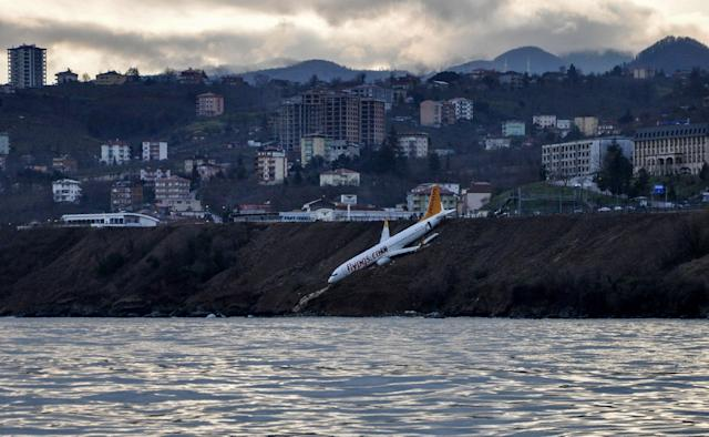 <p>A Pegasus Airlines Boeing 737 passenger plane is seen struck in mud on an embankment, a day after skidding off the airstrip, after landing at Trabzon's airport on the Black Sea coast on Jan. 14, 2018. (Photo: AFP/Getty Images) </p>