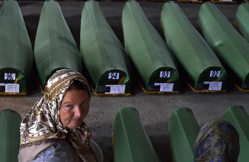 A Bosnian Muslim woman, survivor of the Srebrenica 1995 massacre, searches for remains of her relative among body caskets , laid out at a memorial cemetery in the village of Potocarion near Srebrenica, on July 10, 2014