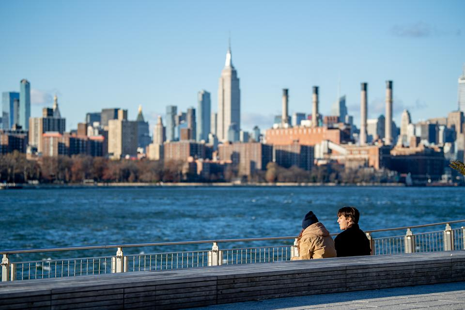 Visitors to Domino Park in Williamsburg, Brooklyn sit on the boardwalk with the Empire State Building in the background during the coronavirus pandemic on November 23, 2020 in New York City.