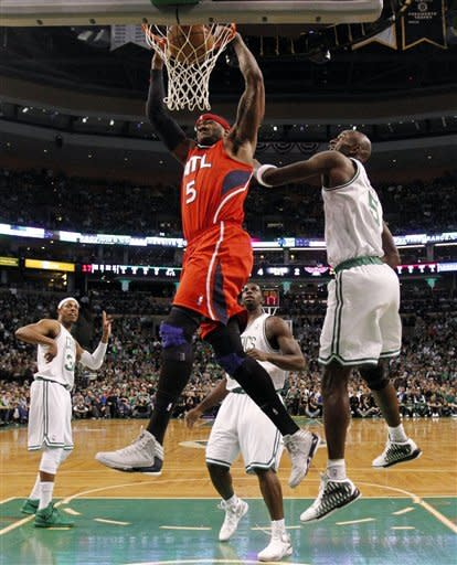 Atlanta Hawks' Josh Smith, center, dunks in front of Boston Celtics' Kevin Garnett, right, during the first half of Game 4 of an NBA basketball first-round playoff series, in Boston on Sunday, May 6, 2012. (AP Photo/Michael Dwyer)