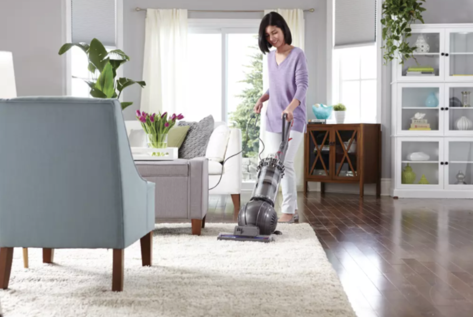 Photo of a woman vacuuming the rug in her living room