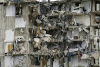 Rubble hangs from a partially collapsed building in Surfside north of Miami Beach