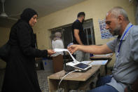 Employees of the Independent High Electoral Commission close a polling station at the end of parliamentary elections, in Baghdad, Iraq, Sunday, Oct. 10, 2021. Iraq closed its airspace and land border crossings on Sunday as voters headed to the polls to elect a parliament that many hope will deliver much needed reforms after decades of conflict and mismanagement. (AP Photo/Hadi Mizban)
