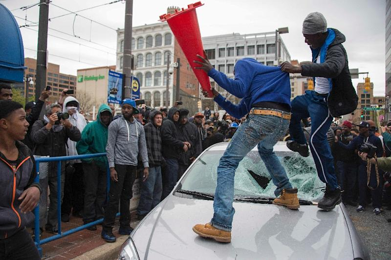 Demonstrators destroy the windshield of a Baltimore Police car on April 25, 2015 as they protest the death of Freddie Gray, an African American man who died of spinal cord injuries while in police custody (AFP Photo/Jim Watson)