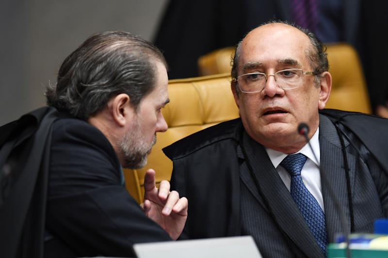 Brazilian Supreme Court judges Gilmar Mendes (R) and Dias Toffoli talk during a session to rule on whether former president Luiz Inacio Lula da Silva should start a 12 year prison sentence for corruption, potentially upending this year's presidential election, at the Supreme Court in Brasilia, on April 4, 2018. Tension soared in Latin America's largest country ahead of the court showdown, with both backers and opponents of Lula -currently the heavy favorite for the October polls- warning of a threat to democracy. / AFP PHOTO / EVARISTO SA (Photo credit should read EVARISTO SA/AFP/Getty Images)