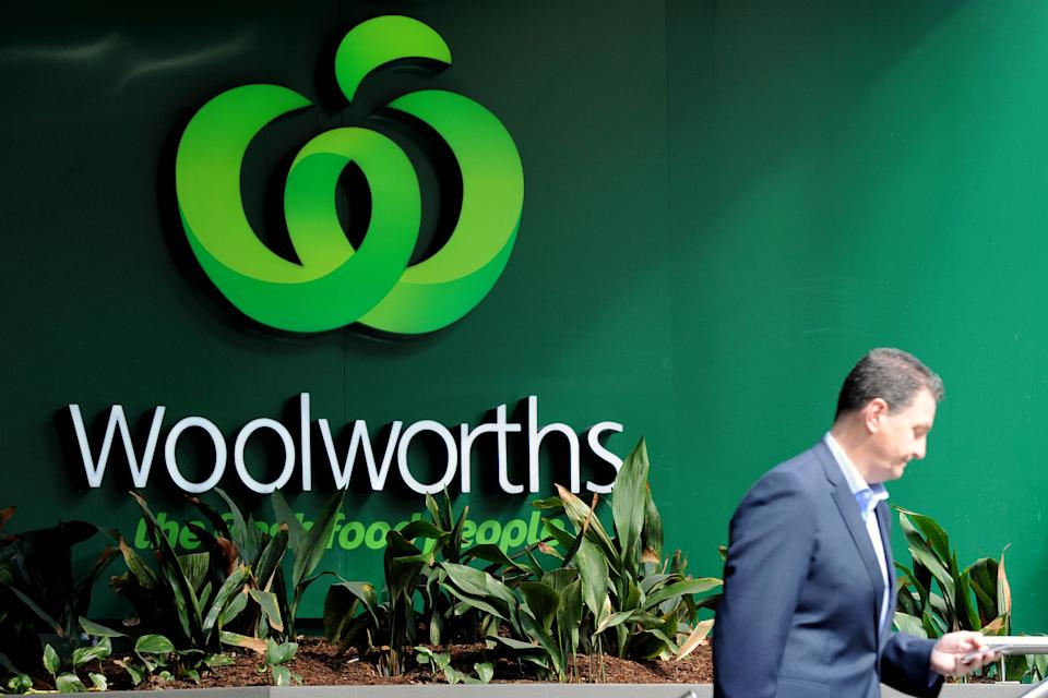 Woolworths customer checks phone while walking outside store. Source: AAP