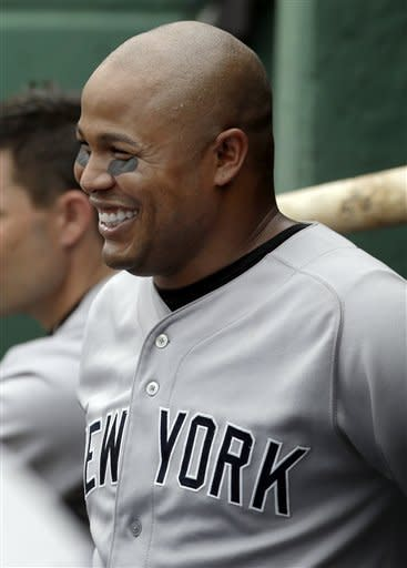 New York Yankees' Andruw Jones smiles in the dugout after hitting his second solo home run against the Boston Red Sox in the fourth inning of the first baseball game in a day-night doubleheader at Fenway Park in Boston Saturday, July 7, 2012. (AP Photo/Elise Amendola)