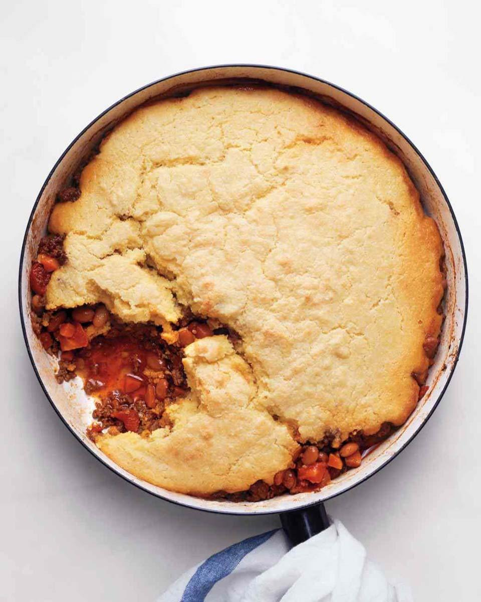 """<p>Buttermilk-infused cornbread combined with classic beef chili puts a new spin on pot pie, creating the perfect comfort food for cozy cool-weather dinners. And just because it's decadent doesn't mean it's difficult. The cornbread topping is simple to whip up and the chili goes back to basics with lean ground beef, canned tomatoes, pinto beans, and some garlic, onion and carrot thrown in for good measure. <a href=""""https://www.yahoo.com/food/cornbread-and-chili-pie-yall-want-to-win-over-97840612570.html"""" data-ylk=""""slk:Get the Cornbread Chili Pie recipe.;outcm:mb_qualified_link;_E:mb_qualified_link;ct:story;"""" class=""""link rapid-noclick-resp yahoo-link""""><b>Get the Cornbread Chili Pie recipe. </b></a></p><p><i>Photo: Marthastewart.com</i></p>"""