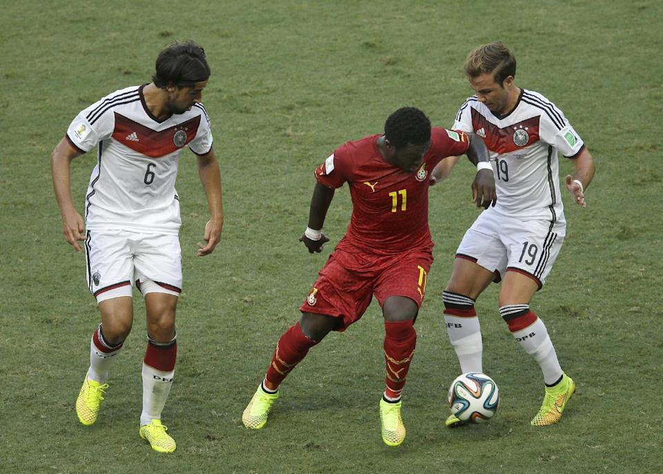Ghana's Sulley Muntari, center, is challenged by Germany's Sami Khedira, left, and Mario Goetze during the group G World Cup soccer match between Germany and Ghana at the Arena Castelao in Fortaleza, Brazil, Saturday, June 21, 2014. (AP Photo/Themba Hadebe)