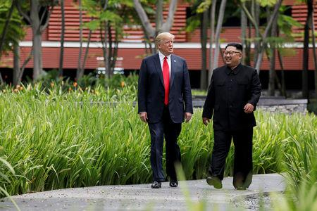 U.S. President Trump and North Korea's Kim walk together before their working lunch during their summit in Singapore