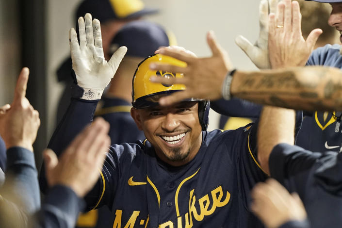 Milwaukee Brewers' Eduardo Escobar celebrates with teammates after hitting a solo home run in the sixth inning of a baseball game against the Cleveland Indians, Friday, Sept. 10, 2021, in Cleveland. (AP Photo/Tony Dejak)
