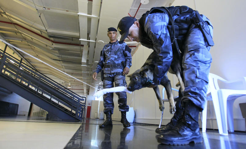 A police officer trains a bomb-sniffing dog near the National Stadium ahead of the Confederations Cup in Brasilia, Brazil, Wednesday, June 12, 2013. The Confederations Cup will start on June 15. (AP Photo/Eugene Hoshiko)