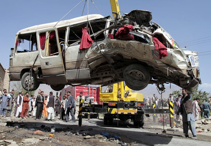 A damaged bus which was hit by a remote control bomb is lifted by a crane on the outskirts of Kabul, Afghanistan, Tuesday, Aug. 7, 2012. A militant detonated a remote-control bomb Tuesday morning, killing at least eight Afghan civilians who were traveling in a bus just northwest of the Afghan capital, police said. (AP Photo/Musadeq Sadeq)