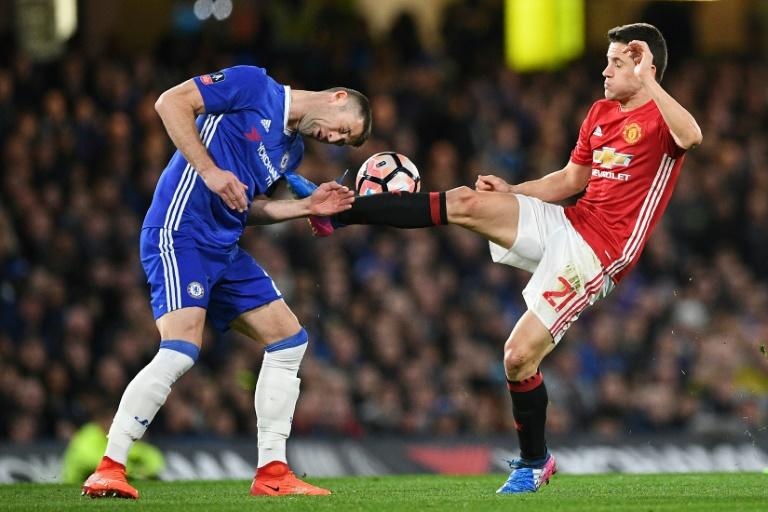 Chelsea's Gary Cahill (L) fights for the ball with Manchester United's Ander Herrera during their English FA Cup quarter-final match, at Stamford Bridge in London, on March 13, 2017