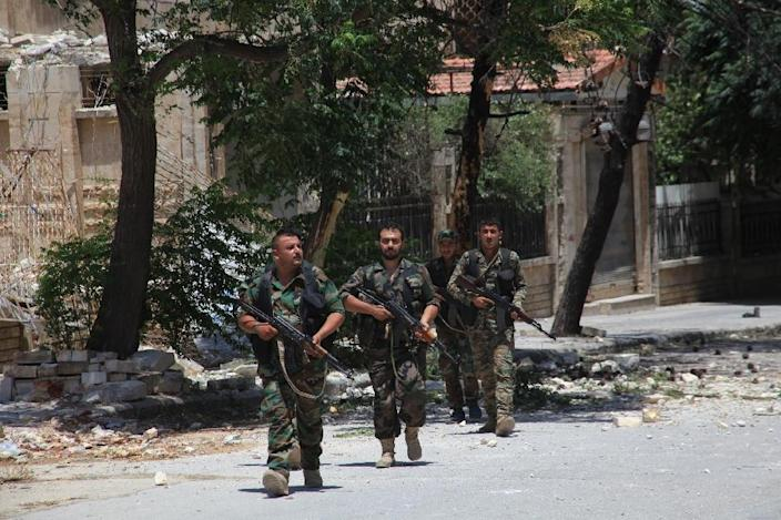 Syrian army soldiers patrol a street in the government-controlled al-Khalidiya area of Aleppo in June (AFP Photo/Georges Ourfalian)