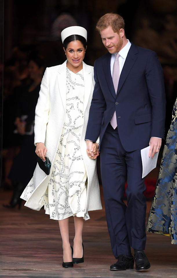 <p>Meghan stunned in an all-white outfit featuring a chain-patterned Victoria Beckham dress, a textured coat, satin pumps, and an emerald clutch at Westminster Abbey on March 11. </p>