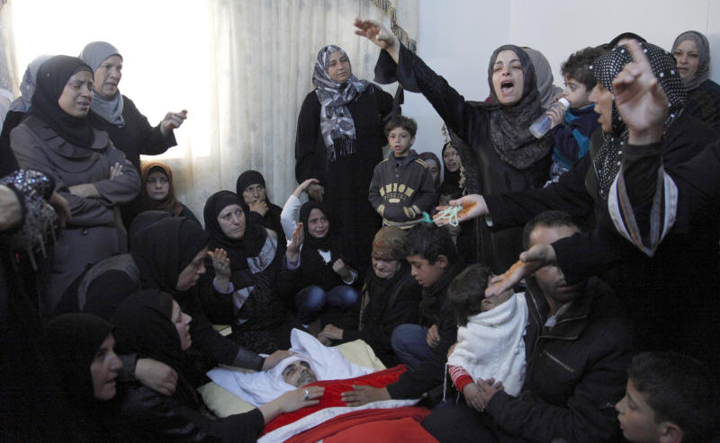 Sister of Qais al Omari, 27, and other relatives, gather around his body, prior to his funeral, Friday Nov. 16, 2012, in Kofr Assad village, Jordan, north of the capital, Amman. Al Omari, 27, was shot by Jordanian police, during a demonstration following an announcement of raising fuel prices, including a hike on cooking gas last Tuesday. (AP Photo/Mohammad Hannon)